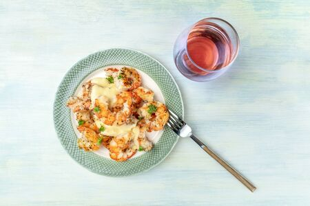 Shrimps with a sauce and a glass of rose wine, shot from above with a place for text