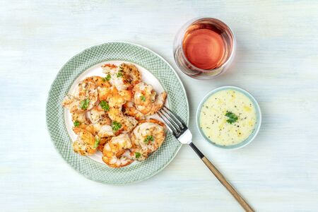 Fried shrimps with a glass of rose wine and a dip, shot from above on a light blue background Reklamní fotografie