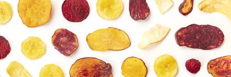 Dry fruit and vegetable chips overhead panoramic shot. Healthy vegan snack, an organic food flat lay pattern on a white background