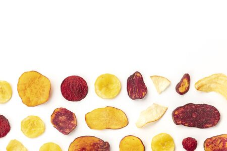 Dry fruit and vegetable chips, shot from the top. Healthy vegan snack, an organic food flat lay pattern on a white background with a place for text