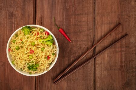 A bowl of soba noodles with vegetables and a red pepper, shot from the top on a dark rustic wooden background with chopsticks and a place for text