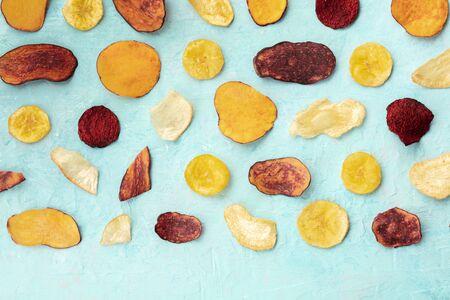 Chips de frutas y verduras secas, snack vegano saludable, un patrón laico plano de alimentos orgánicos sobre un fondo azul con espacio de copia