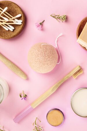 Plastic-free, zero waste cosmetics, flat lay pattern on a pink background. Bamboo toothbrushes and cotton swabs, konjac sponge, etc, shot from the top