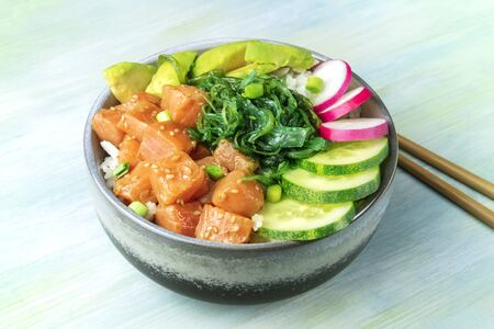 A bowl of salmon poke with avocado, wakame and cucumber on a teal blue background