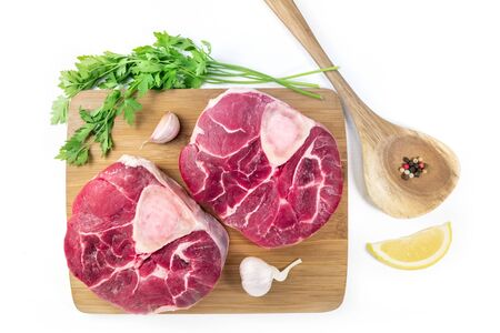Ossobuco veal shanks with parsley, lemon and garlic for a gremolata, typical Italian Lombard cuisine ingredients, flay lay on a white background