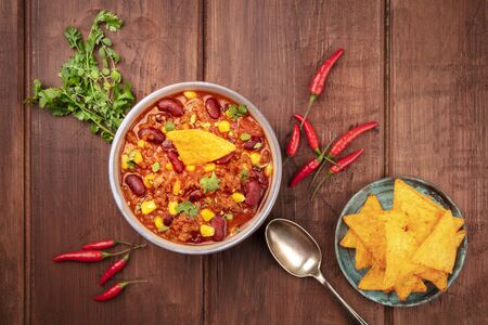 Chili con carne, shot from the top on a dark rustic wooden background with ingredients and nachos