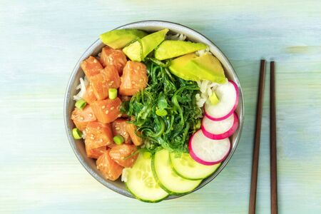 Salmon poke with avocado, wakame and cucumber, shot from the top on a teal blue background with chopsticks