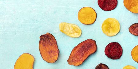 A panorama of dry fruit and vegetable chips, shot from the top on a vibrant teal blue background with copy space