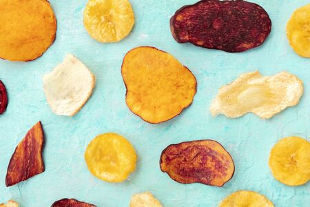 Dry fruit and vegetable chips, top shot. Healthy vegan snack, an organic food flat lay pattern on a teal blue background