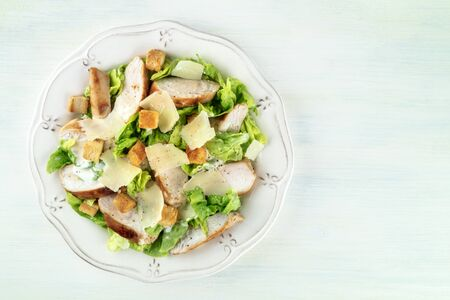 Chicken Caesar salad. Slices of chicken breast, green lettuce, Parmesan cheese, and croutons, overhead shot with a place for text 写真素材