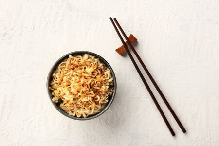 Instant soba noodles with scallions, carrot, and a sauce, shot from above with chopsticks and a place for text Stock Photo