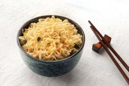 Instant soba noodles with carrot and scallions, a close-up with chopsticks and copy space
