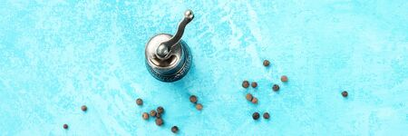A panorama of allspice, Jamaica pepper. Scattered peppercorns with a vintage pepper mill, shot from above on a turquoise background with copy space. Culinary flat lay design template