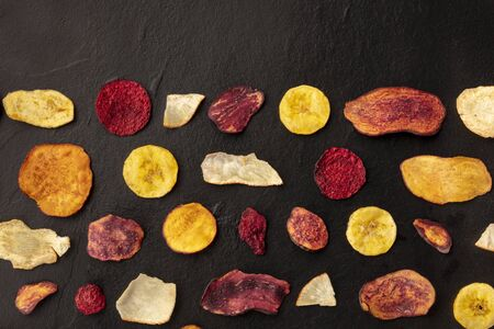 Dry fruit and vegetable chips, shot from the top on a black background with a place for text. Healthy vegan snack, an organic food flat lay pattern with copy space
