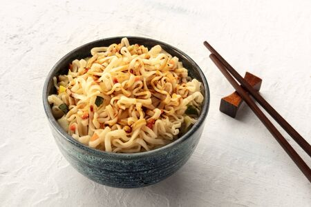 Instant soba noodles with carrot, scallions, and a sauce, a close-up shot with chopsticks and a place for text