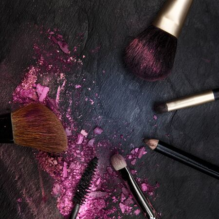 Make-up brushes with crushed cosmetics, overhead square shot on a black background forming a framewith a place for text, a beauty design template for a makeup banner