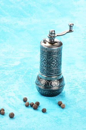 Allspice, Jamaican pepper. Scattered peppercorns with a vintage pepper mill on a turquoise blue background with a place for text Фото со стока