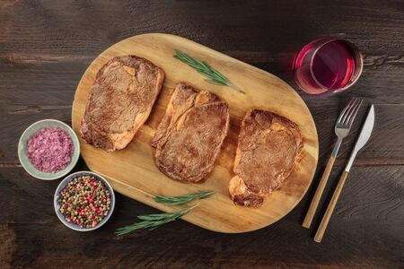 Beef fillet steaks, shot from above on a dark rustic wooden background with rosemary, salt, pepper, and wine Stock fotó