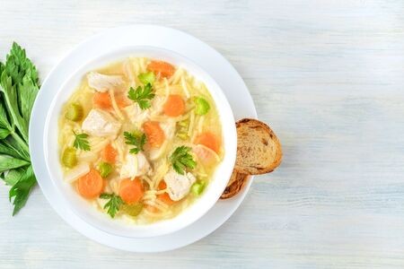 Chicken noodle soup, shot from above with toasted bread and a place for text