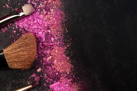 Make-up brushes and crushed cosmetics, shot from above on a black background with a place for text, a beauty design template for a makeup banner