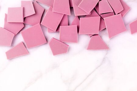 Ruby chocolate slices, shot from above on a white marble background with a place for text