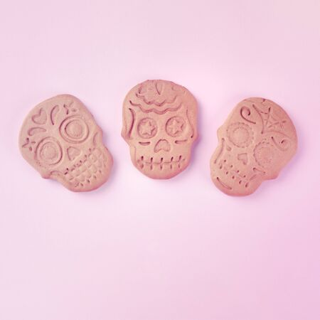 Day of the Dead concept. Three homemade ginger cookies in the shape of skulls, overhead square shot on a pink background with copy space Stock Photo