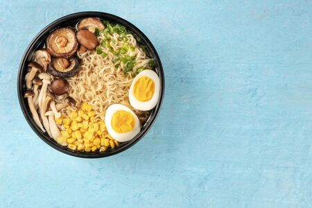 Ramen. Soba with eggs, mushrooms, and vegetables, shot from the top on a blue background with a place for text Stockfoto
