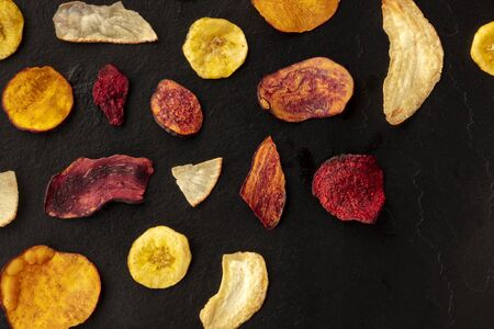Driedf fruit and vegetable crisps, top shot with a place for text. Healthy vegan snack, an organic food flat lay pattern on a black texture