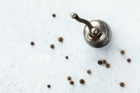 Allspice, Jamaican pepper. Black peppercorns with a vintage pepper mill, shot from the top with copyspace