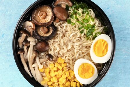 Ramen close-up. Soba with eggs, mushrooms, and vegetables, shot from above on a blue background