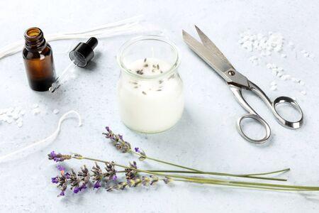 Handgemaakte lavendel geurkaars met etherische olie, bloemen, was en wieken. Een ambachtelijk kerstcadeau Stockfoto