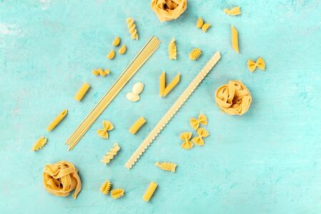 Italian pasta of various sorts, a flat lay banner, shot from above on a teal blue background with a place for text