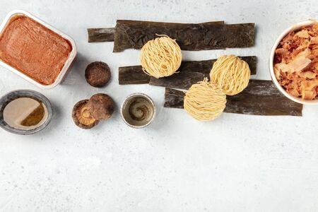 Ramen ingredients. Dried sea vegetable kelp, soba, miso paste, bonito flakes, shiitake mushrooms, sake, mirin, overhead shot, a flat lay composition with copy space