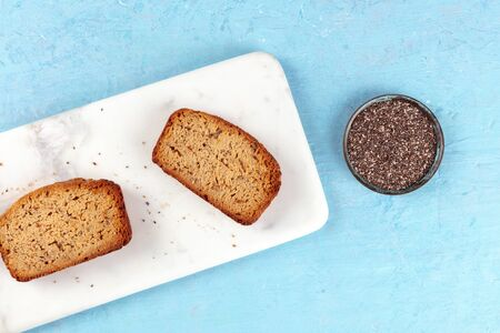 Chia seed cake slices, shot from the top on a marble cutting board and a blue background with a place for text, healthy vegan baking
