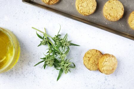 Cannabis butter cookies with marijuana buds and cannaoil, homemade healthy biscuits, shot from the top