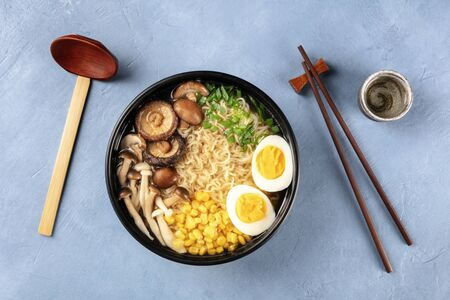 Ramen. Soba with eggs, mushrooms, and vegetables, shot from the top with sake, traditional wooden spoon, and chopsticks