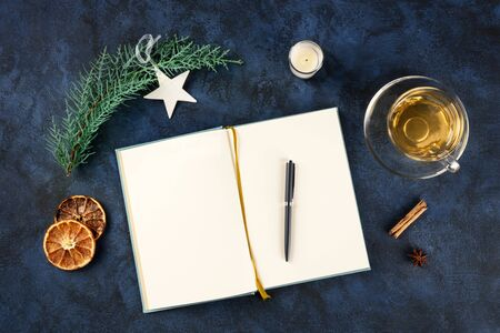 New Year resolutions, flat lay top shot with a place for text, on a dark blue background with Christmas decorations, a pen, and a cup of tea