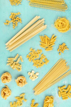 Italian pasta flat lay poster, shot from above on a blue background. Spaghetti, penne, farfalle and other types, top view Reklamní fotografie