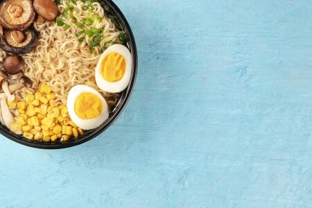 Ramen close-up. Soba noodles with eggs, mushrooms, and vegetables, overhead shot from on a blue background with copy space