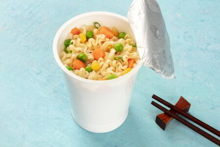 Ramen noodles cup close-up, instant noodles in a plastic cup on a blue background with chopsticks and copy space