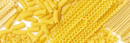 Italian pasta texture, flat lay banner, overhead panoramic shot on a white background. Fusilli, farfalle, macaroni, spaghetti, macaroni and other types