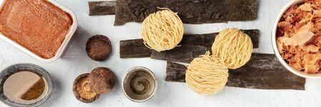 Ramen ingredients panorama. Dried sea vegetable kelp, soba, miso paste, bonito flakes, shiitake mushrooms, sake, mirin, overhead shot, a flat lay composition Reklamní fotografie