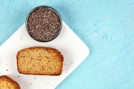 Chia seed cake, shot from the top on a marble cutting board and a blue background with a place for text, healthy vegan baking