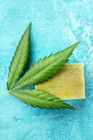 A cannabis leaf with homemade hemp soap bar, shot from above on a turquoise blue background with a place for text Reklamní fotografie