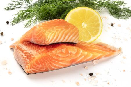Slices of salmon with lemon and dill, close-up with salt and pepper, cooking fish, on a white background