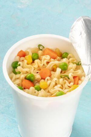 Ramen cup close-up, instant noodles in a plastic cup on a blue background Reklamní fotografie