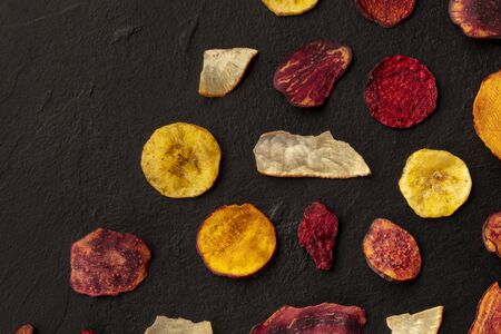 Dried fruit and vegetable crisps, overhead shot with a place for text. Healthy vegan snack, an organic food flatlay pattern on a dark texture