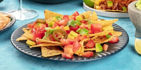 Nachos with avocado and tomato, with jalapeno peppers and cilantro leaves, a panoramic close-up shot