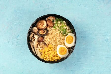 Ramen. Soba noodles with eggs, mushrooms, and vegetables, overhead shot on a blue background