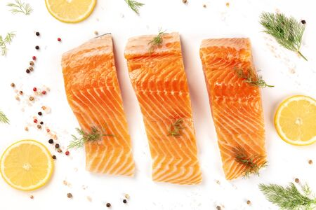 Slices of salmon with lemon and dill, shot from the top with salt and pepper, cooking fish, on a white background, a flat lay composition Reklamní fotografie